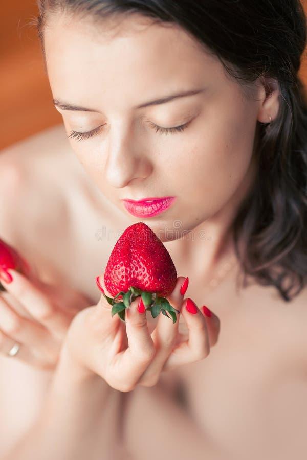 Fotografia uwodzicielska żeńska łasowanie truskawka, zbliżenie portret ponowny fotografia stock