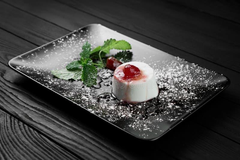 Fotografia włoski panny cotta deser z truskawkowym sirup i mennica leaf na czarnym drewnianym tle zdjęcie royalty free