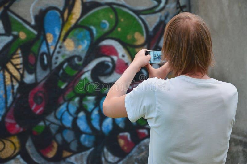Fotografia w trakcie rysunkowych graffiti na starej betonowej ścianie fotografia stock