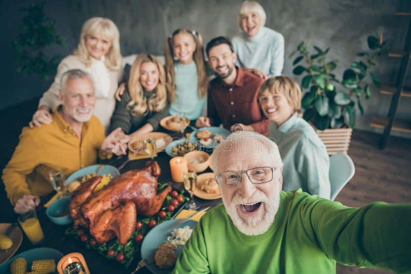 Fotografia wielkiej rodziny siedzącej przy stole z przytulnymi daniami wokół pieczonego indyka, wielonarodowego krewnego siwego d zdjęcia royalty free