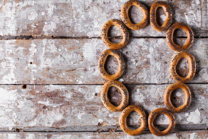 Fotografia wyśmienicie bagels kropiący z makowymi ziarnami tła drewniany lekki fotografia royalty free