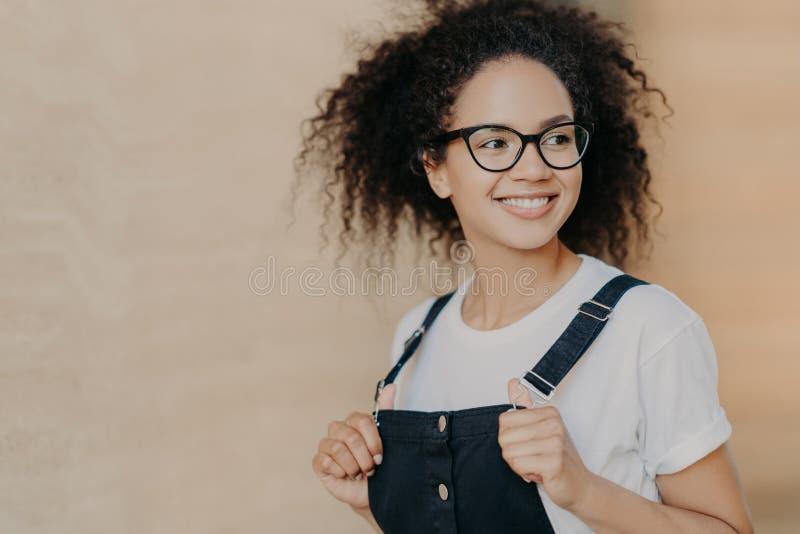Fotografia zadowolonego Afro Amerykański nastolatek z kędzierzawym włosy, uśmiechy szeroko, spojrzenia daleko od, jest ubranym pr zdjęcie royalty free