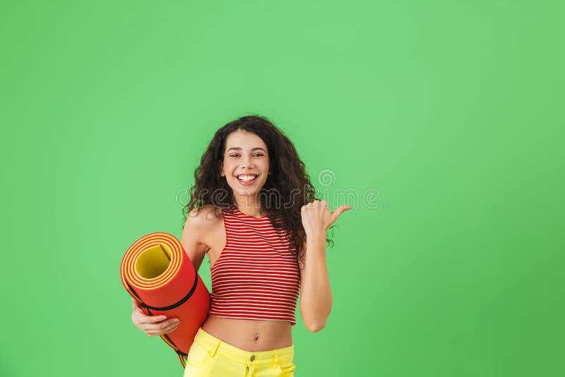 Fotografia zdrowa kobieta 20s uśmiecha się joga matę i niesie podczas treningu zdjęcie royalty free