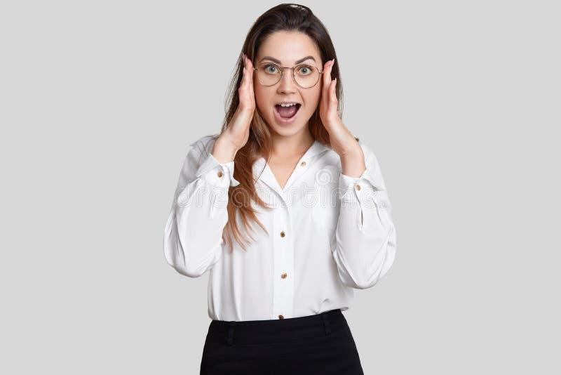 Fotografia zdumiewająca kobieta utrzymuje oba ręki na głowie, otwiera usta szeroko, reaguje na nagłej wiadomości w biurze, ubiera obraz stock