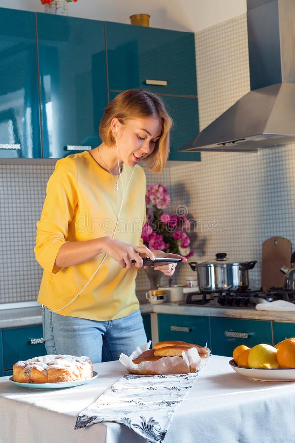 Fotografias bonitas da mulher uma torta caseiro Dona de casa moderna com a tabuleta na cozinha imagens de stock royalty free