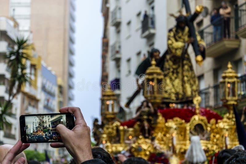 Fotografias de um homem com seu telefone celular a procissão de Jesus o Nazarene em Huelva, Espanha imagens de stock