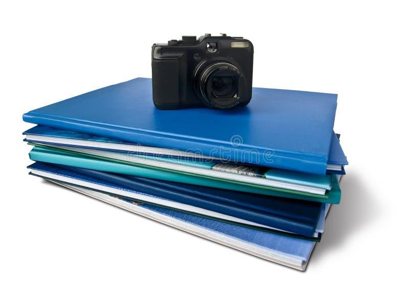 Fotografiböcker med en kamera över dem fotografering för bildbyråer