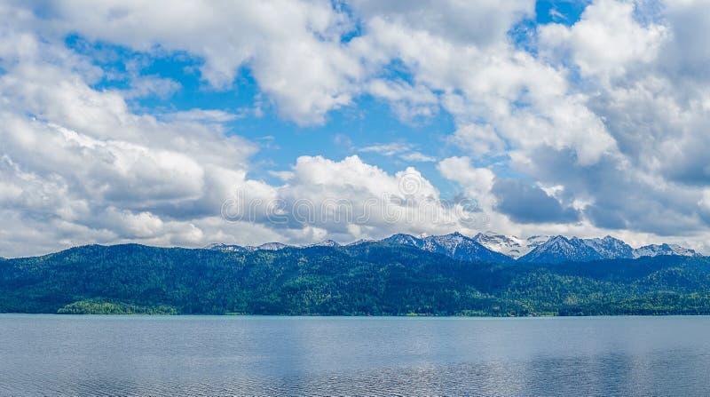 Fotografie an einem See mit Ansicht zu den Bergen und zum bewölkten Himmel stockfoto