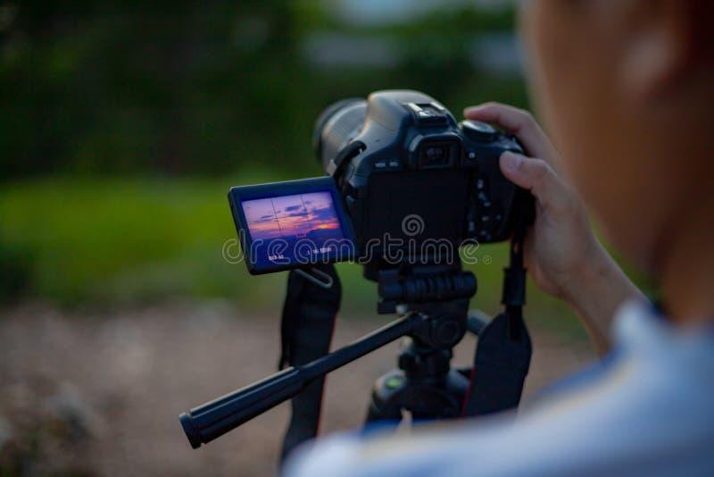 Fotografiemann ein Foto der Landschaft des Sonnenunterganghintergrundes machen stockfotos