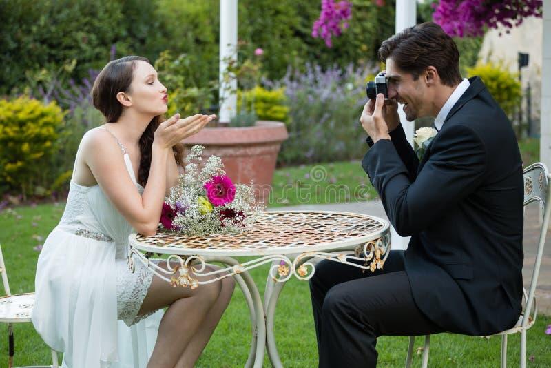 Fotografierender Schlagkuß der Braut des Bräutigams beim im Park bei Tisch sitzen stockfotografie