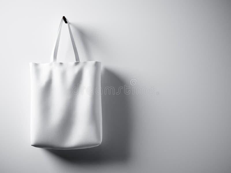 Fotografii bawełnianej tkaniny białej torby wisząca lewa strona Pusty betonowej ściany tło Wysoce szczegółowa tekstura, przestrze royalty ilustracja
