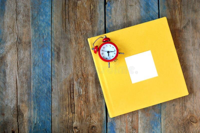 Fotografii książkowa pokrywa z pustą ramą i zegarem na drewnianym tle zdjęcia royalty free
