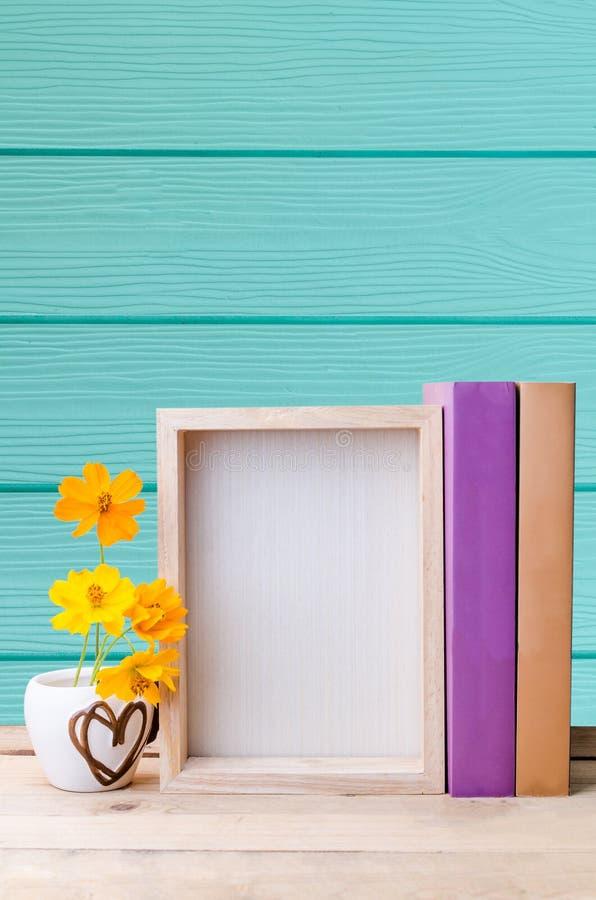 Fotografii rama, rezerwuje i kwitnie na drewnianym stole z błękitem zaleca się obraz stock