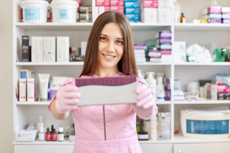 Fotografii s kobiety lekarki mienia pudełko medycyna, jest ubranym różaną medyczną togę, seansu pudełko z zastrzykami, być w apte zdjęcia royalty free