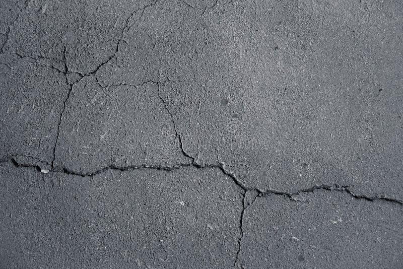 Fotografii tekstura jezdnia, kamień lub granit, asfalt z wielkimi cząsteczkami, szara autostrada z wielkim pęknięciem w środku zdjęcia stock