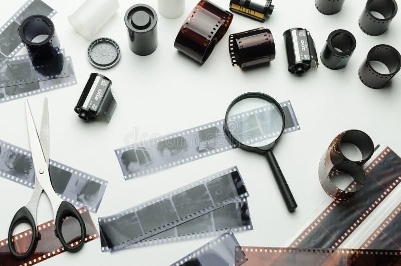 Fotografiska filmer, sax och förstoringsglas på vit bakgrund arkivfoto