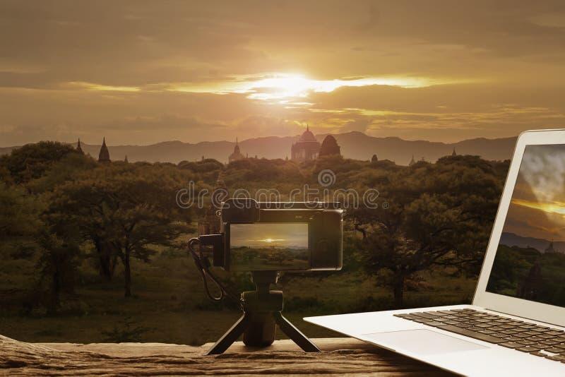 Fotografiutrustning Digital kamera på den mini- tripoden och bärbara datorn med härligt landskap av Myanmar bakgrund, lopp och royaltyfri bild