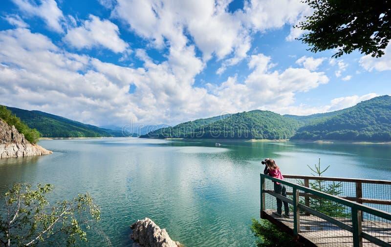 Fotografkvinnlig på sjön Vidraru Carpathians Rumänien royaltyfria foton