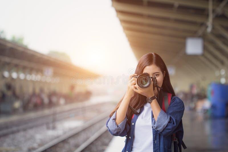 Fotografmädchenlächeln-Holdingdigitalkamera Junger Asiatinreisender mit der Kamera, die Fotos auf Untergrundbahnplattform macht lizenzfreie stockfotos