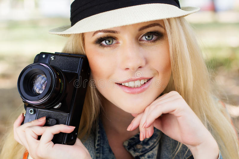 Fotografo biondo piacevole della ragazza con la macchina fotografica immagini stock