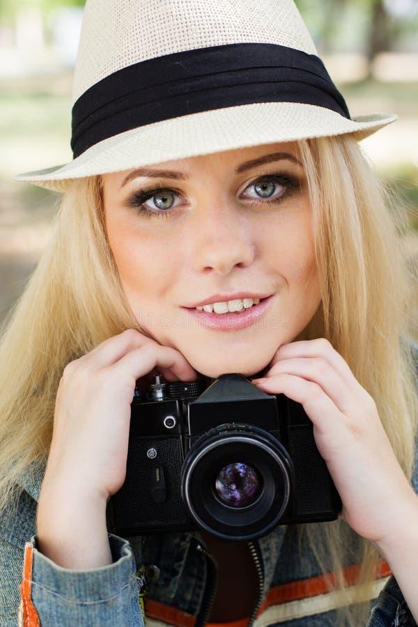 Fotografo biondo piacevole della ragazza con la macchina fotografica fotografia stock