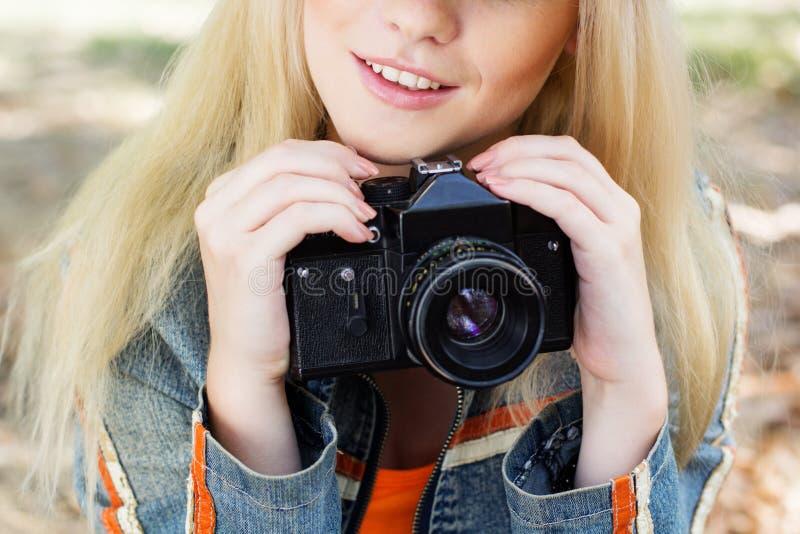Fotografo biondo piacevole della ragazza con la macchina fotografica fotografie stock