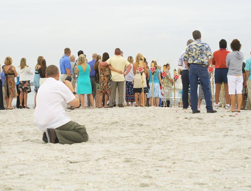 Fotografo che cattura le foto del gruppo sulla spiaggia immagine stock libera da diritti