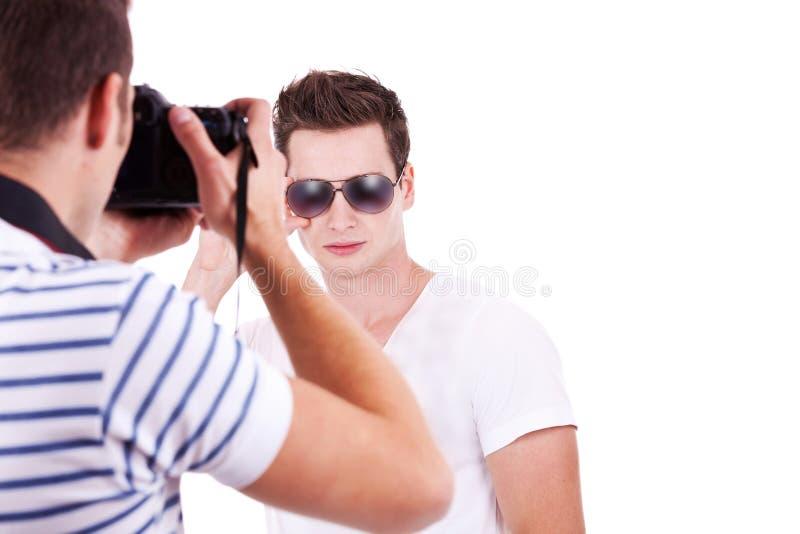 Fotografo che cattura una maschera del suo modello maschio fotografie stock