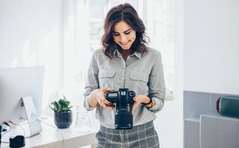 Fotografo che controlla le immagini sulla macchina fotografica del dslr immagine stock