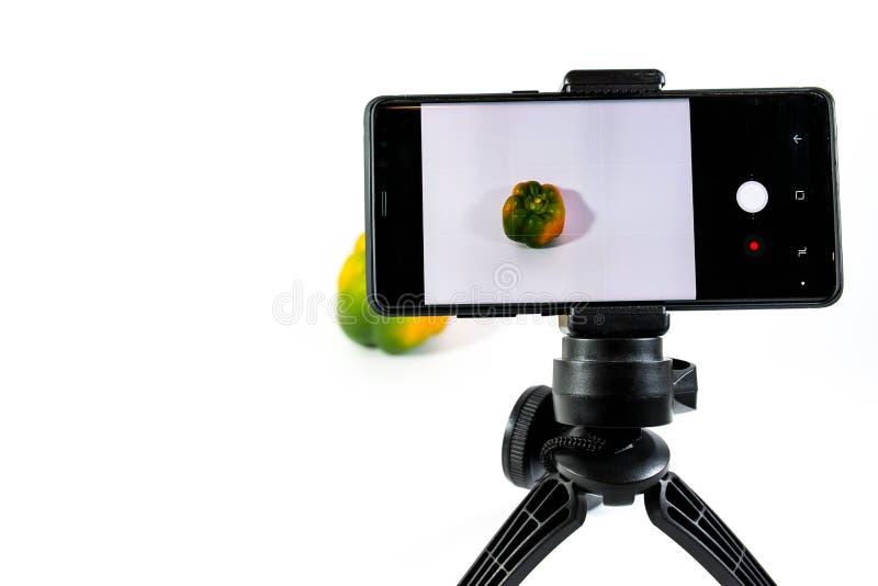 Fotografo che crea immagine con un telefono cellulare moderno sul pepe giallo di piccolo verde del treppiede a fuoco immagine stock libera da diritti