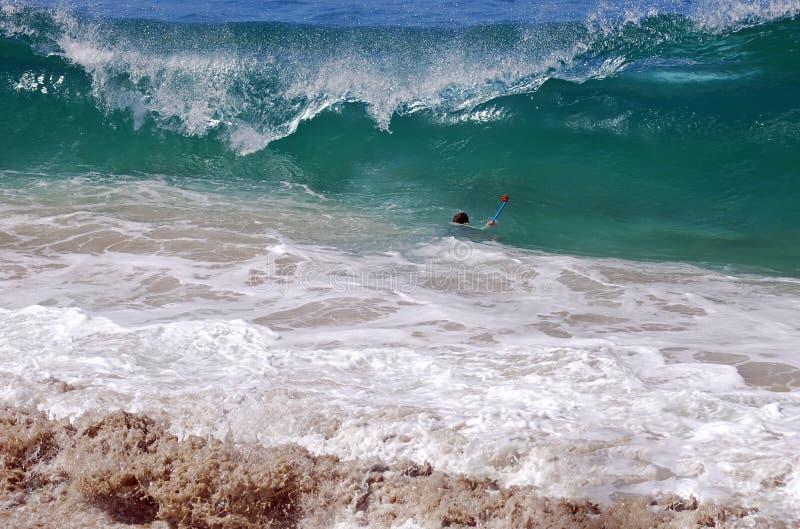 Fotografo che fotografa un'onda con una camma di GoPro fotografia stock