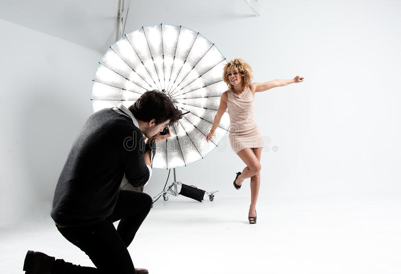 Fotografo che lavora con un modello sveglio in uno studio professionale fotografia stock libera da diritti