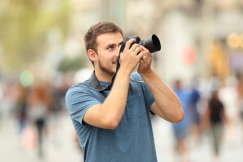 Fotografo che prende le foto sulla via con una macchina fotografica del dslr fotografia stock libera da diritti