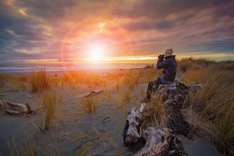Fotografo che prende una foto di tramonto sulla spiaggia del mare immagini stock libere da diritti