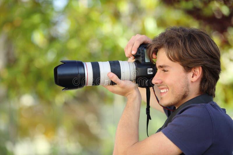 Fotografo che prende una fotografia all'aperto con una macchina fotografica del dslr fotografia stock