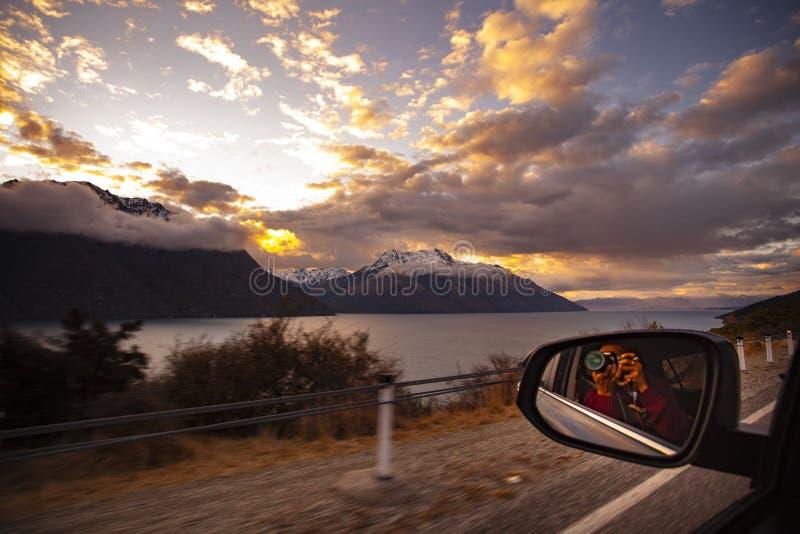 Fotografo che prende una fotografia del cielo di tramonto mentre un drivi dell'automobile immagini stock