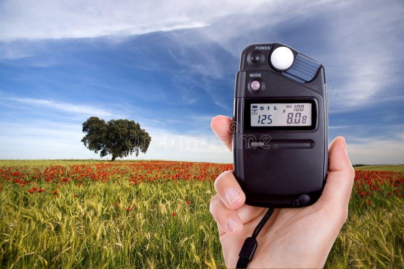 Fotografo che usando esposimetro per misurare indicatore luminoso fotografia stock libera da diritti