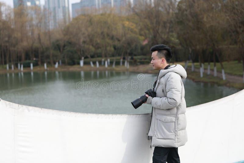 Fotografo cinese asiatico dell'uomo in parco fotografia stock