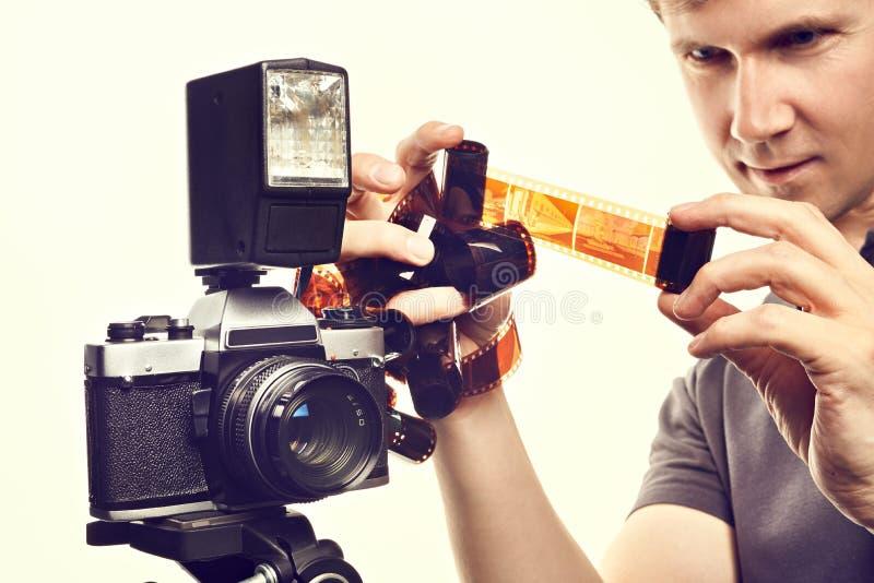 Fotografo con le pellicole negative di colore vicino alla macchina fotografica di SLR isolata immagine stock libera da diritti