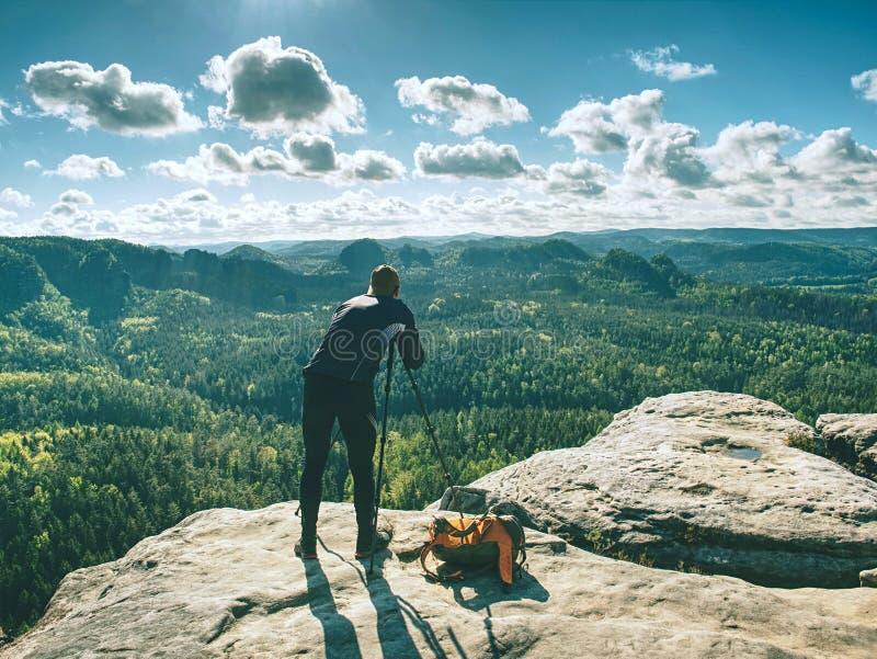 Fotografo dell'uomo che prende immagine di paesaggio quando treppiede stabilito fotografia stock