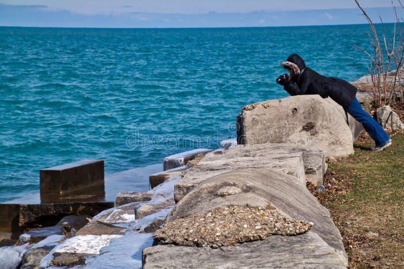 Fotografo della donna che cattura le onde che spruzzano dal lago Michigan immagine stock