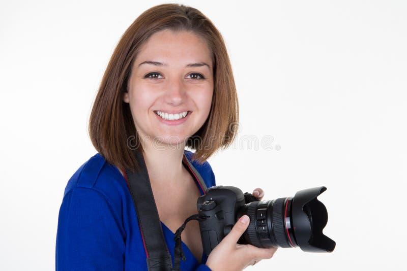 Fotografo della donna che tiene sorridere del dslr della macchina fotografica reflex immagine stock