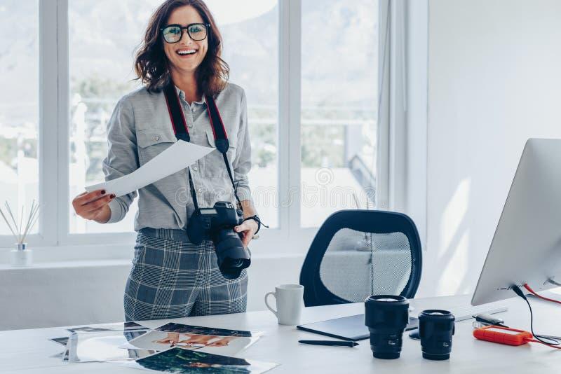 Fotografo della giovane donna al suo ufficio immagini stock libere da diritti