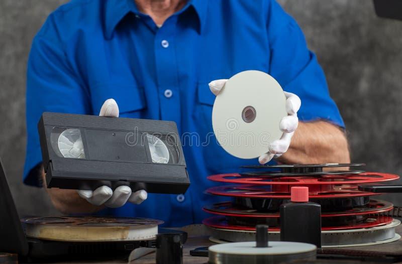 Fotografo della mano che tiene il nastro di VHS ed il disco di DVD per la conversione fotografie stock