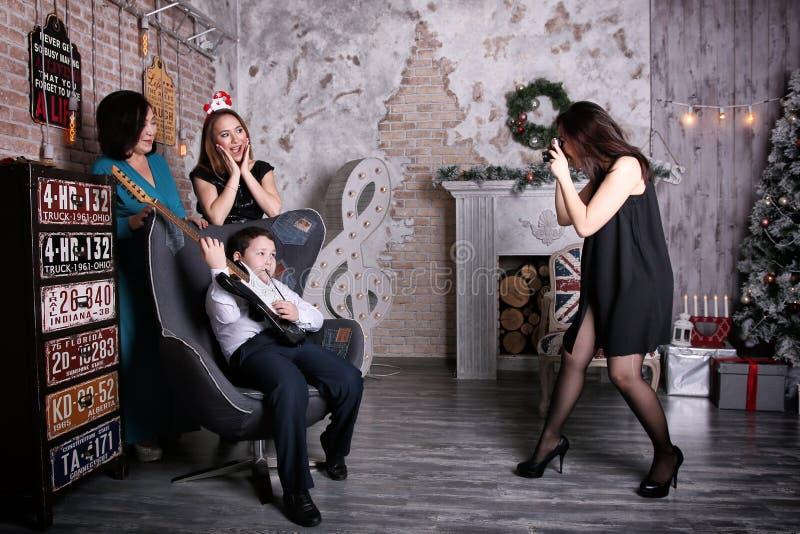 Fotografo della ragazza che fotografa la famiglia nell'interno festivo fotografie stock