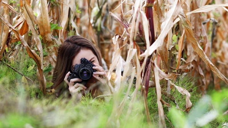 Fotografo della ragazza con capelli scompigliati scuri che si trovano nell'erba e nel cereale appassito e tiri su una macchina fo fotografia stock libera da diritti