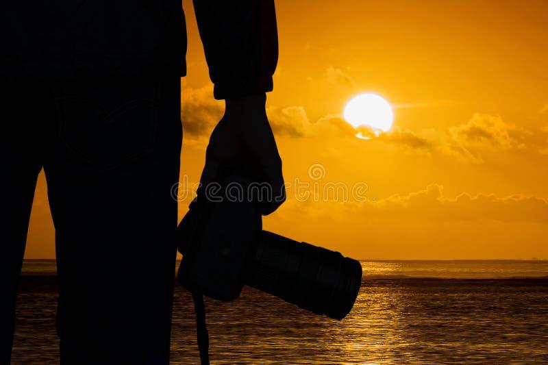 Fotografo della siluetta con la macchina fotografica ed il tramonto fotografia stock