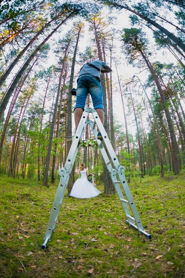 Fotografo di nozze che per mezzo della scala a libro per fare le immagini della sposa fotografia stock libera da diritti