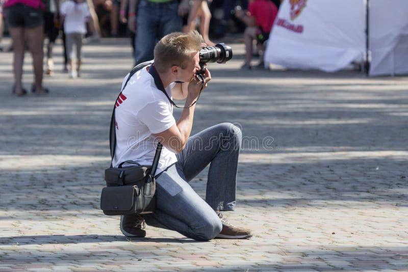 Fotografo di via che osserva tramite il mirino il modello fotografie stock