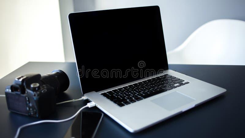 Fotografo e progettista del posto di lavoro, computer portatile con la macchina fotografica e smartphone sulla tavola fotografia stock